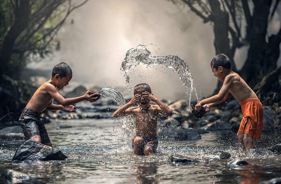 suda oynayan üç çocuk